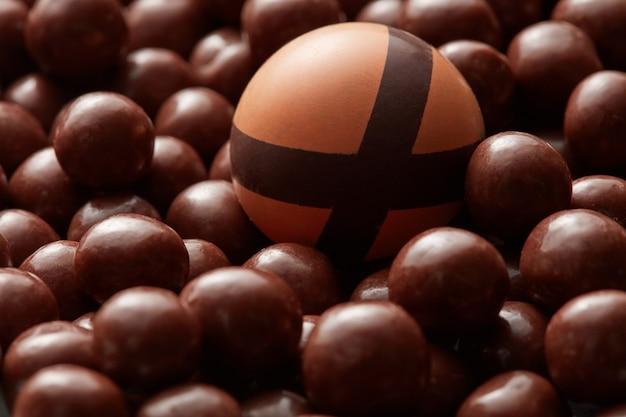 Żółty cukierek na tle czekoladowych kulek