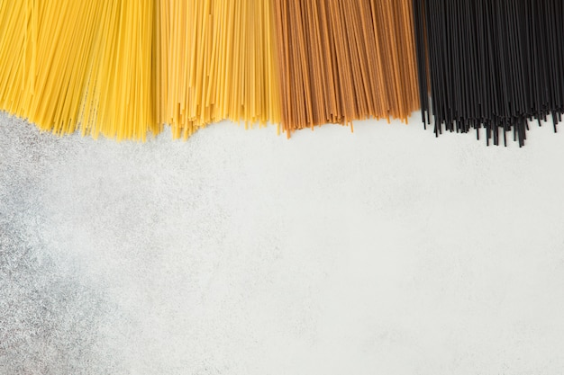 Żółty długi spaghetti na szarym tle. włoski makaron z różnych odmian pszenicy i różnych kolorów. odgórny widok surowy spaghetti, karmowy tła flatlay pojęcie.