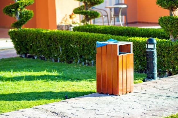 Żółty drewniany kosz na śmieci na zewnątrz na chodniku w parku. pojemnik na śmieci na ulicy na zewnątrz.