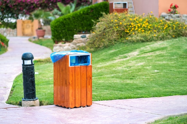 Żółty drewniany kosz na śmieci na zewnątrz na chodniku w parku. pojemnik na śmieci na zewnątrz.
