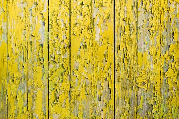 Żółty drewniany płot z pęknięciami i starą farbą.