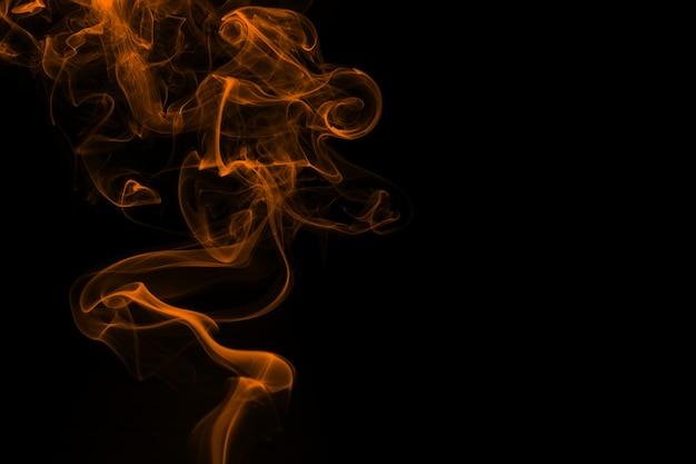 Żółty dym streszczenie na czarnym tle, żółty atrament na ciemny