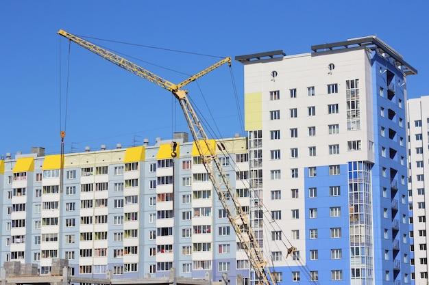 Żółty dźwig i błękitne niebo na placu budowy