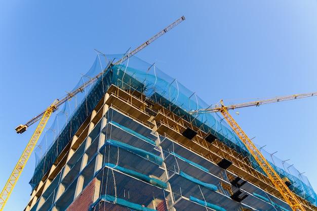 Żółty dźwig na placu budowy do podnoszenia dużych ciężarów materiałów budowlanych i do murarzy, aby ukończyli swoją pracę.
