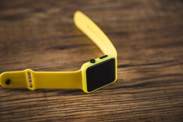 Żółty elegancki zegarek na drewnianym stole