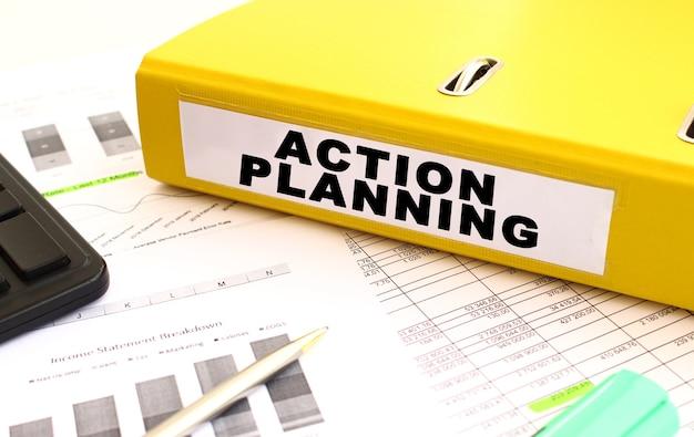 Żółty folder dokumentów z tekstem planowania działań na biurku nad wydrukowanymi wykresami