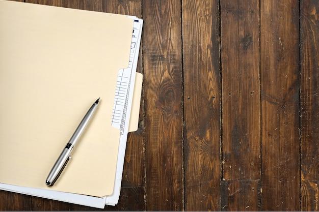 Żółty folder i długopis na drewnianym tle