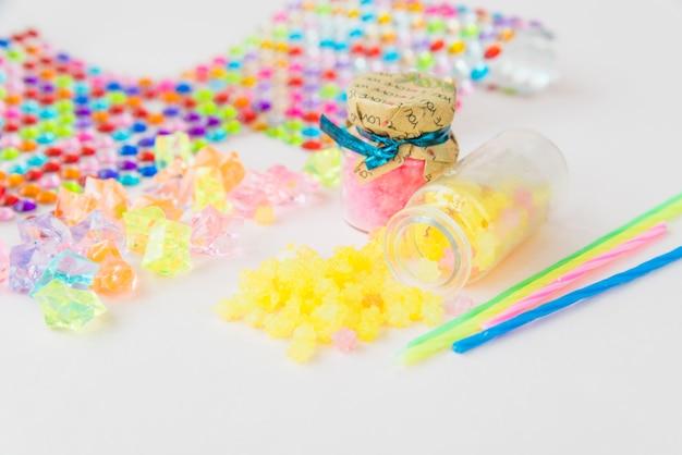 Żółty galaretowy świeczka wosk rozlewa od butelki na białym tle
