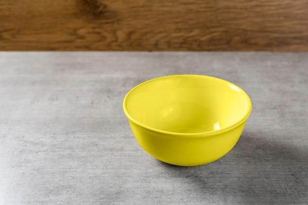 Żółty garnek miski umieścić lody lub owoce na tle drewniany stół