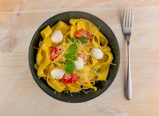 Żółty gotowany makaron pappardelle, fettuccine lub tagliatelle na czarnym talerzu widok z góry.