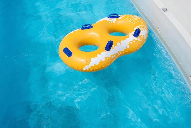 Żółty gumowy pierścień unoszący się na orzeźwiającej niebieskiej wodzie