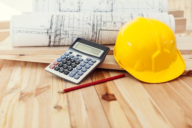 Żółty hełm z planami i kalkulatorem na drewnie