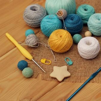 Żółty i niebieski szydełko i kulki bawełnianej nici na drewnianym stole, miejsce.