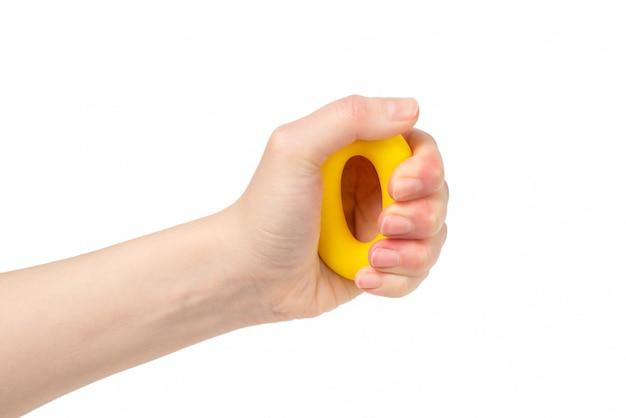Żółty i pomarańczowy expander w kobiety ręce odizolowywającej na bielu