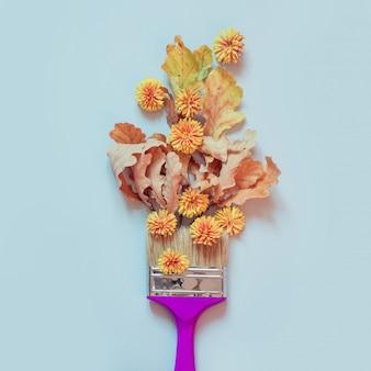 Żółty jesień kwiat, dębów susi liście i farby muśnięcie na błękicie. moda minimalna.