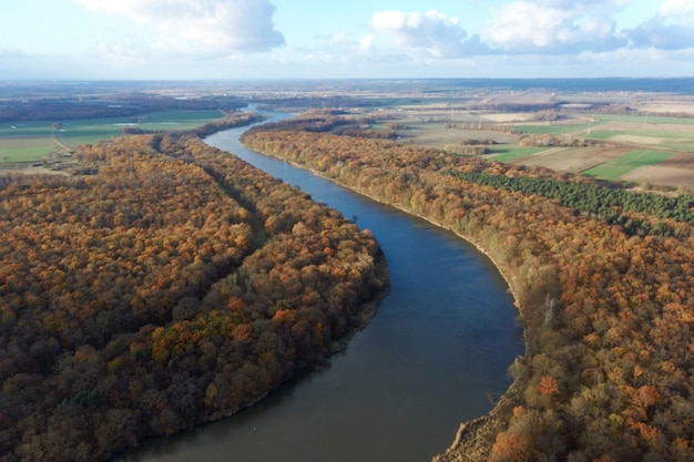 Żółty jesienny las i błękitna rzeka, widok z góry, jesienny krajobraz