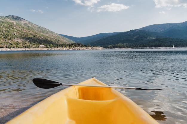 Żółty kajak i wiosłować na jeziorze w słoneczny dzień. koncepcja czasu letniego i sportu. nikt