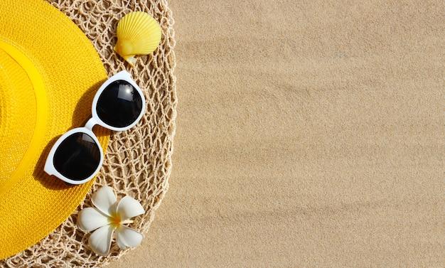 Żółty kapelusz letni z okularami przeciwsłonecznymi na piasku. widok z góry