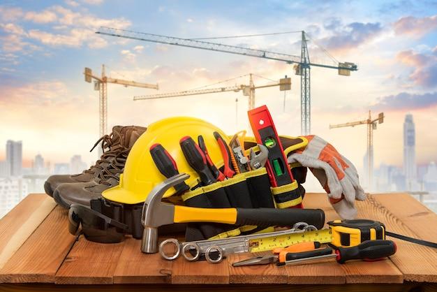 Żółty kask do prac budowlanych i narzędzi z dźwigiem w tle.