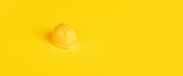 Żółty kask robotników zabawek na żółtym tle, koncepcja konstrukcji minimalizmu, obraz panoramiczny