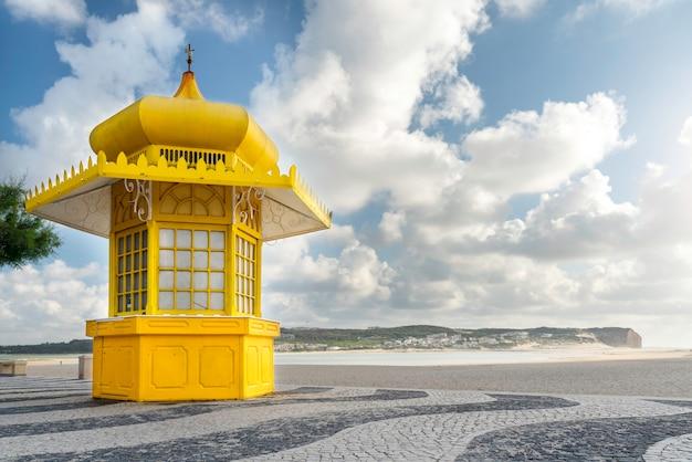 Żółty kiosk na tradycyjnej portugalskiej utwardzonej promenadzie przed plażą foz do arelho w caldas da rainha portugalia