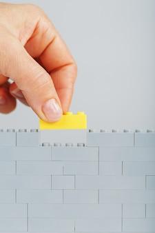 Żółty klocek kładzie dłoń na szarej ścianie zabawki