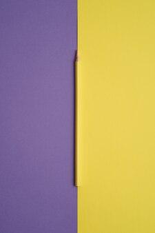 Żółty kolorowy ołówek na białym tle na fioletowy i żółty stół