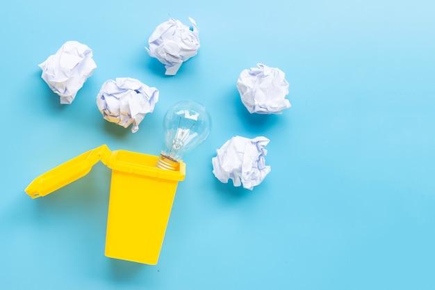 Żółty kosz z żarówką i biały zmięty papier na niebieskiej powierzchni. pomysły i koncepcja kreatywnego myślenia