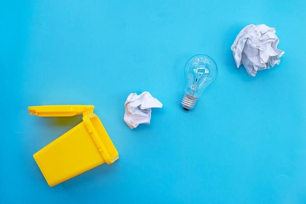 Żółty kosz z żarówką i biały zmięty papier na niebieskim tle. pomysły i koncepcja kreatywnego myślenia. widok z góry