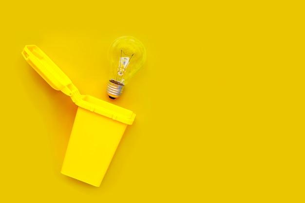 Żółty kosz z żarówką na żółtym tle. pomysły i koncepcja kreatywnego myślenia.