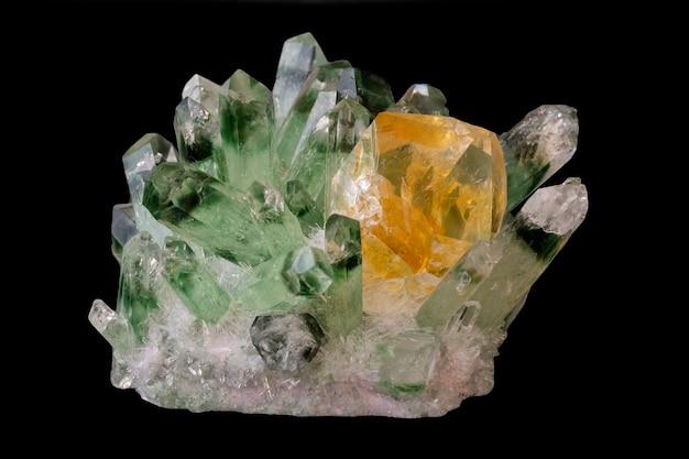 Żółty kryształ cytrynowy wśród zielonych kryształów kwarcu odizolowanych na czarno. minerały geologiczne