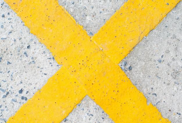 Żółty krzyż symbol na drodze