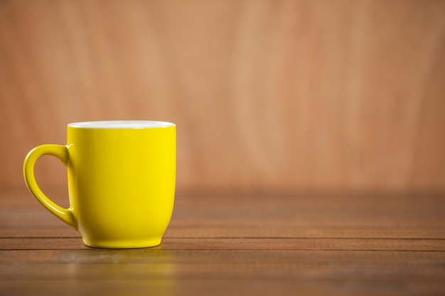 Żółty kubek kawy na drewnianym stole