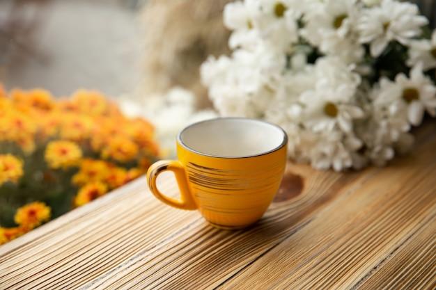 Żółty kubek na drewnianej powierzchni na rozmytym tle z kwiatami