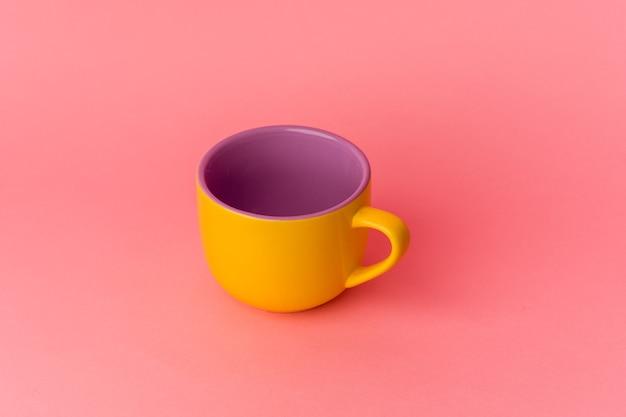 Żółty kubek na różowym tle