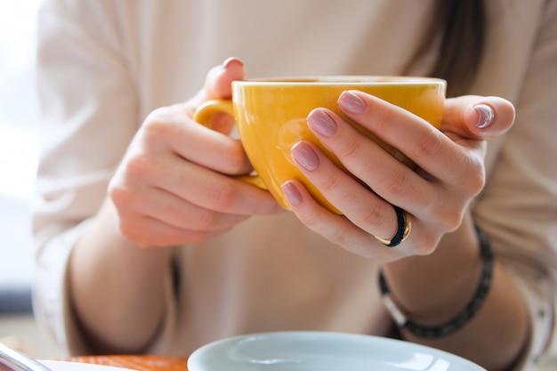 Żółty kubek w rękach młodej kobiety. dziewczyna trzyma filiżankę kawy w kawiarni. przerwa na kawę, śniadanie.