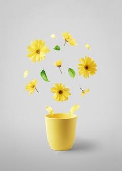 Żółty kubek z latającymi żółtymi kwiatami na szarym stole. pojęcie wiosny.