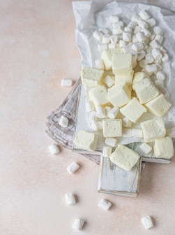 Żółty kwadratowy kształt pianki i biały waniliowy marshmallow na drewnianej desce do krojenia
