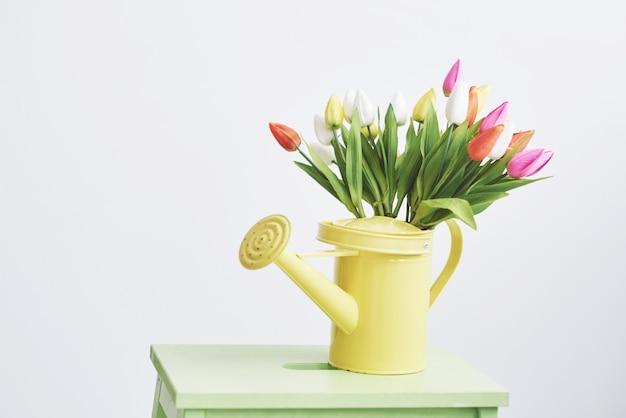 Żółty lejek z małymi kolorowymi kwiatami. piękne wiosenne kwiaty