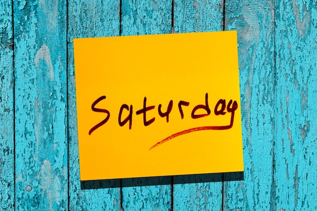 Żółty lepki liść na ścianie. napis znacznik słowo sobota