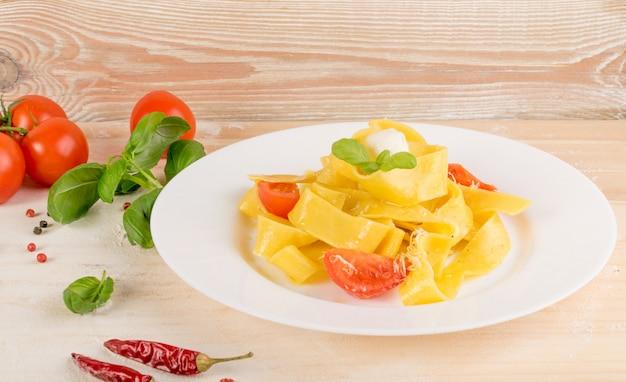 Żółty makaron gotowany pappardelle, fettuccine lub tagliatelle na białym talerzu z bliska. domowy makaron wstążka jajeczna lub makaron z pomidorami, bazylią i kulkami mozzarelli na drewnianym tle rustykalnym