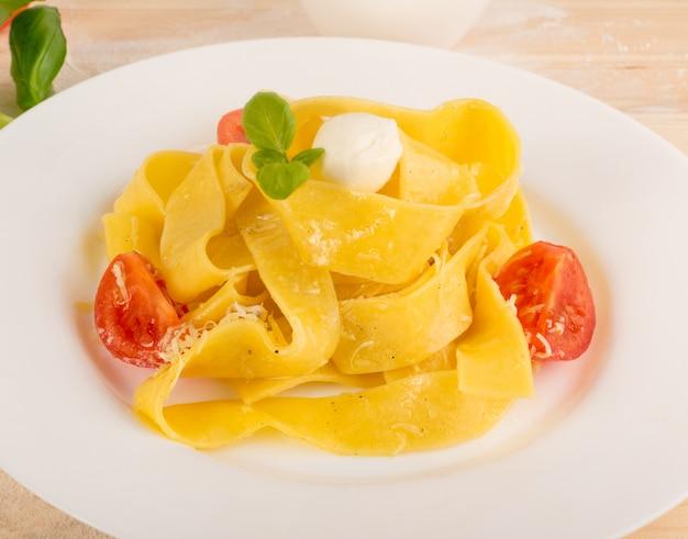 Żółty makaron gotowany pappardelle, fettuccine lub tagliatelle na białym talerzu z bliska.
