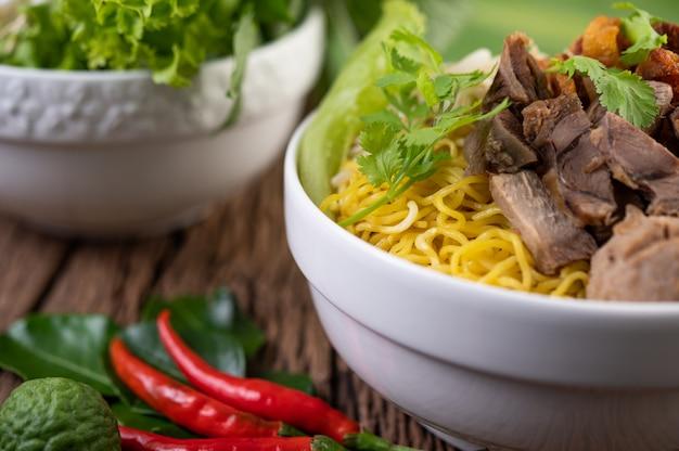 Żółty makaron w filiżance z chrupiącą wieprzowiną, plasterkami wieprzowiny i klopsikami wraz z tajskim makaronem w stylu kulinarnym