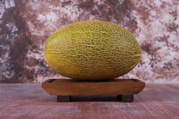 Żółty melon na drewnianym talerzu na różowym w środku.