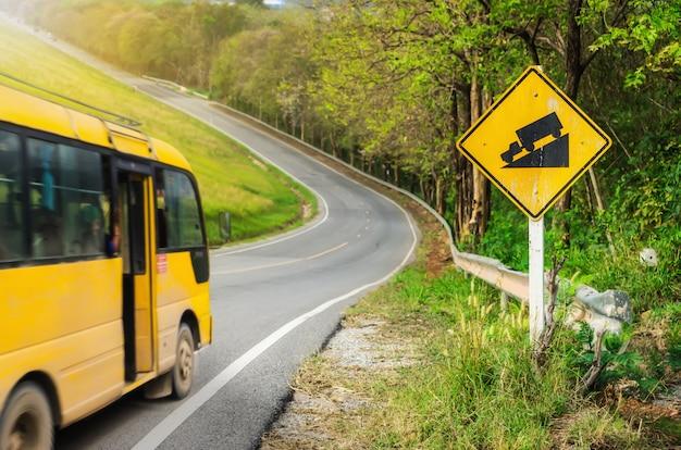 Żółty mikro autobus na drodze i znak drogowy ostrzegawczy strome zbocza.
