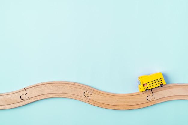 Żółty model autobusu szkolnego i drewniana droga