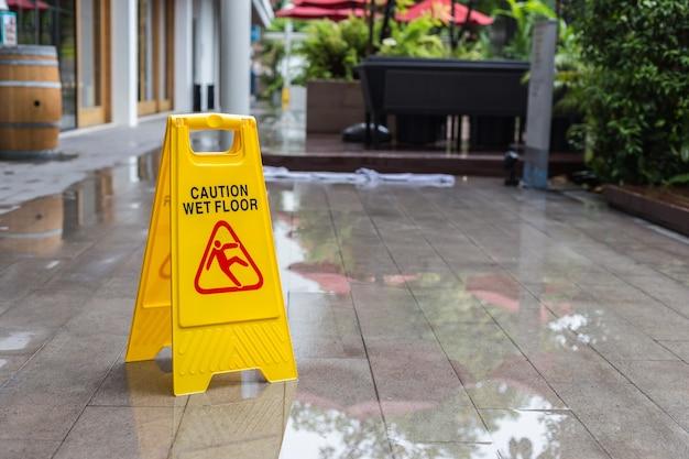 Żółty mokry podłogowy znak ostrzegawczy na podłoga w hotelowym korytarzu