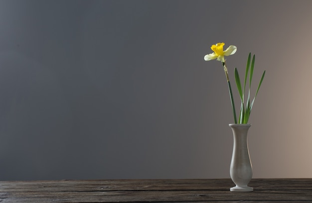 Żółty narcyz w wazonie na drewnianym stole na ciemnej powierzchni