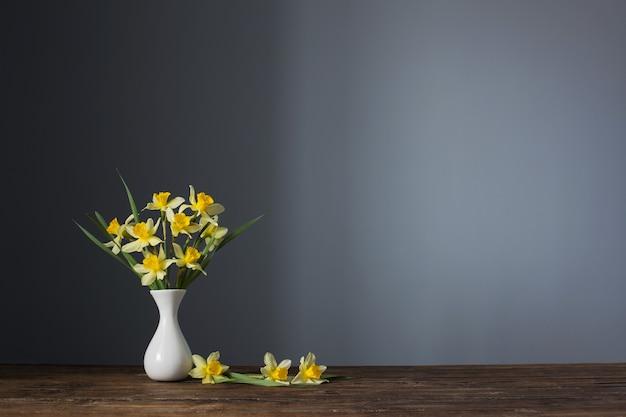 Żółty narcyz w wazonie na drewnianym stole na ciemnym tle