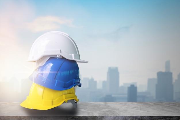 Żółty, niebieski i biały kask ciężki kapelusz budowy pracy na stole cementu w górnej części pokładu budynku i miasta w tle